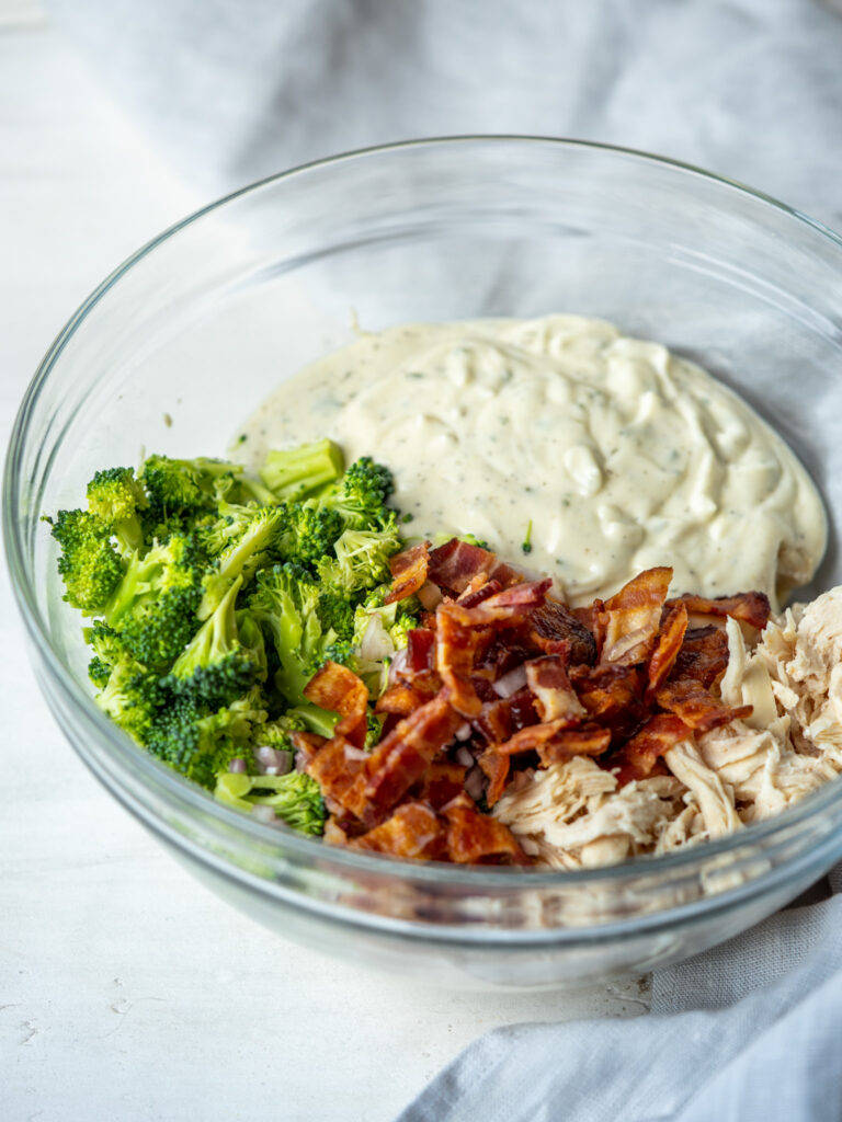 Three quarter view of a bowl of ingredients for ranch chicken salad