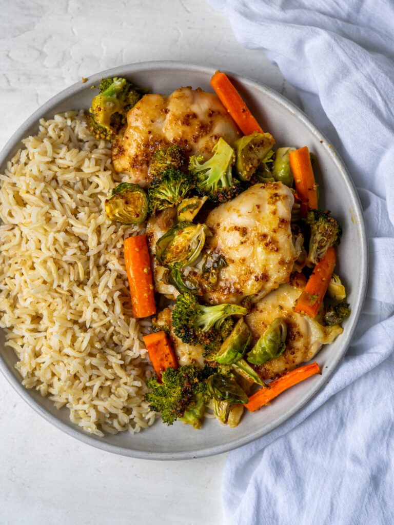 cooked sheet pan chicken and veggies on a plate with brown rice