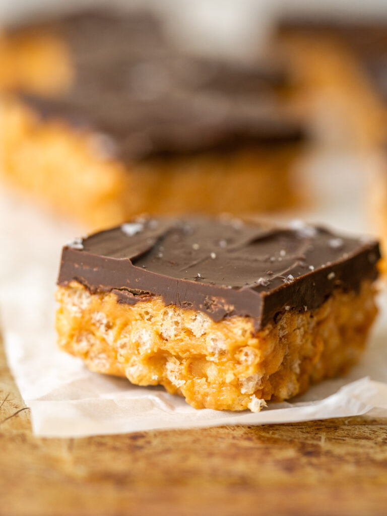 Close up side view of a peanut butter chocolate rice krispie bar.