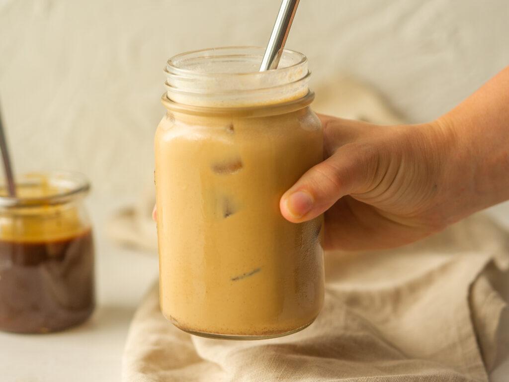 Side view of a hand grabbing an iced pumpkin spice latte made with starbucks pumpkin sauce