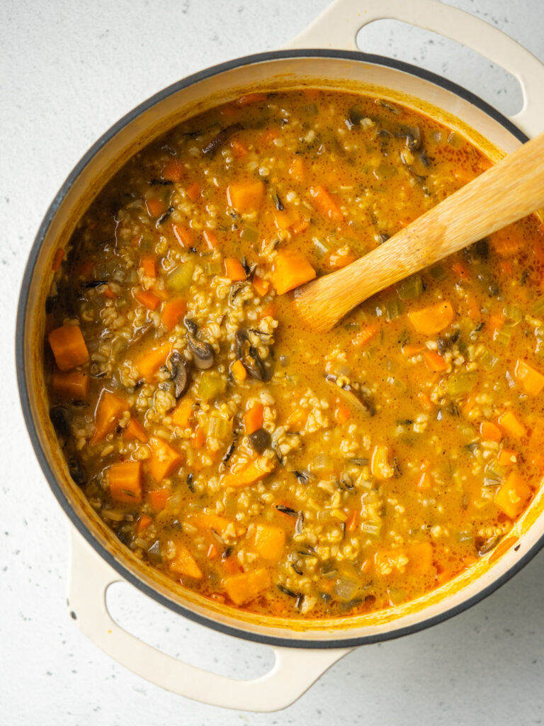 Above view of wild rice soup in a dutch oven with a wooden serving spoon