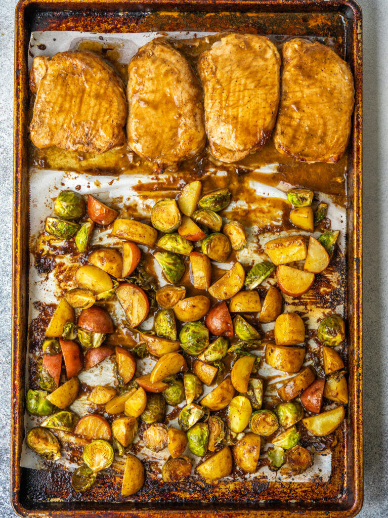 Above view of a baked pork chop dinner on a baking sheet