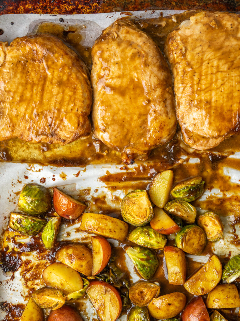 Close up above view of baked pork chop dinner on a baking sheet
