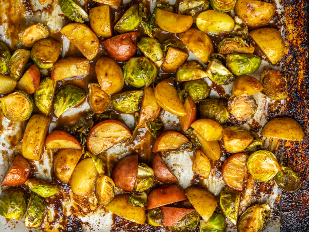 Close up above view of roasted potatoes and brussels sprouts from the pork chop sheet pan dinner