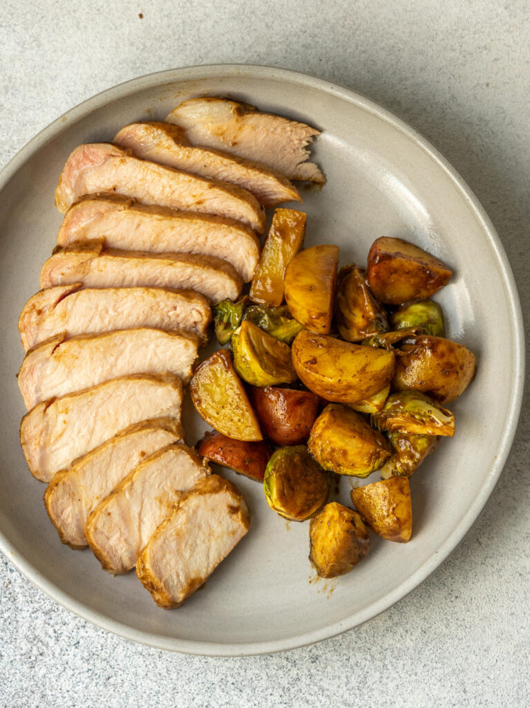 Above view of juicy sliced pork chops on a serving plate with potatoes and brussels sprouts