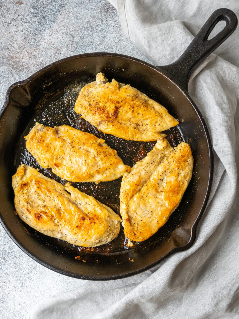 above view of boneless chicken breast in a cast iron skillet