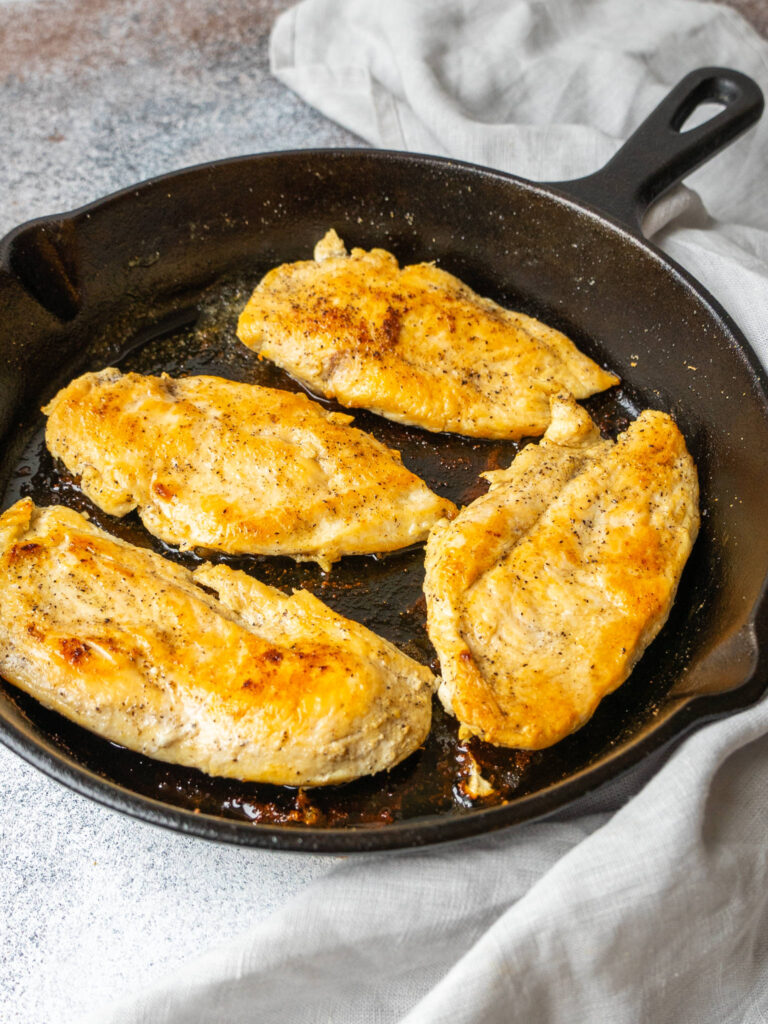 three quarter view of cooked chicken breasts in a cast iron skillet