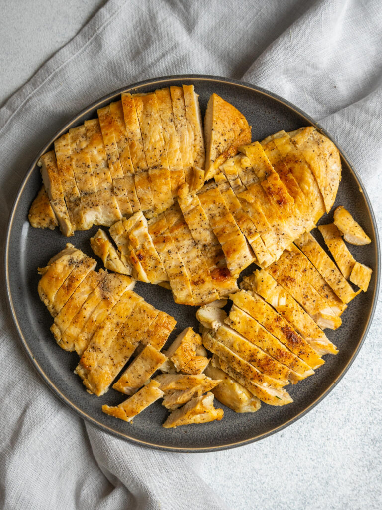 above view of sliced pan seared chicken breasts on a plate