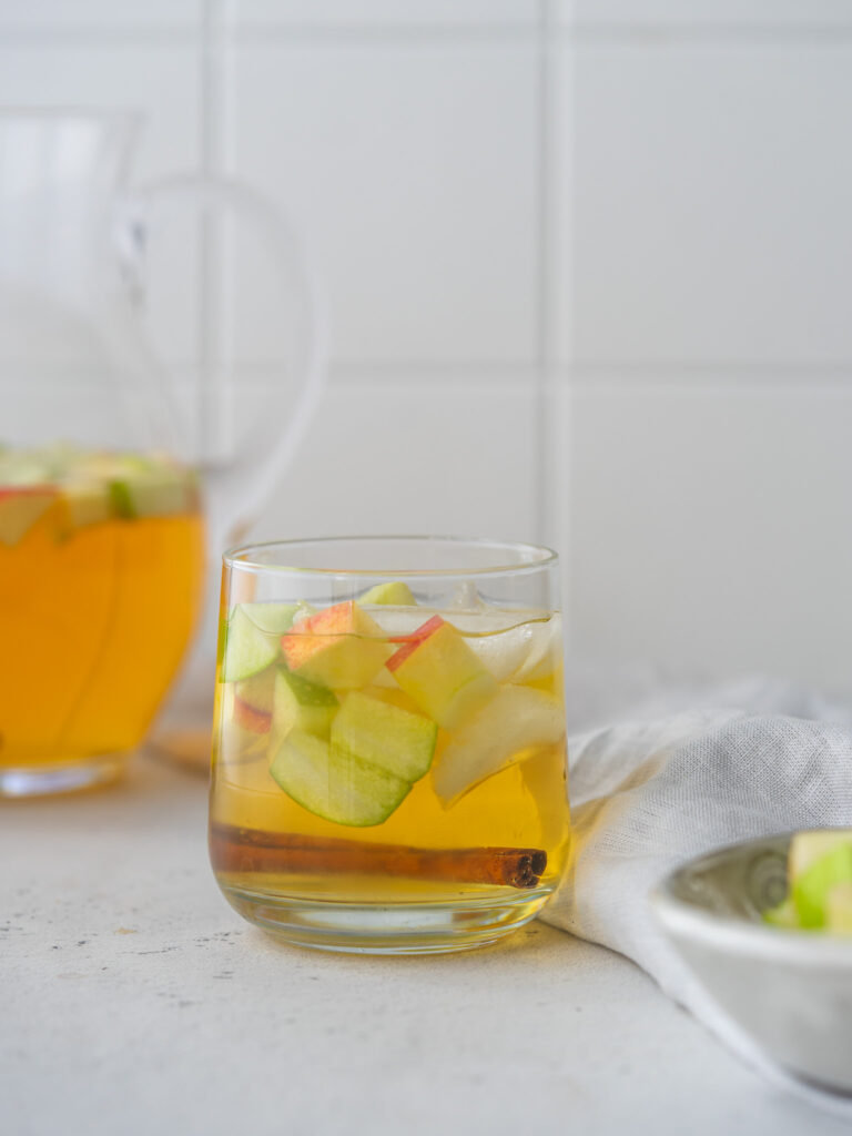 Side view of sparkling apple cider cocktail in a serving glass with cubed apple pieces