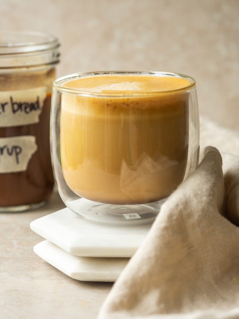 Gingerbread latte in a mug next to a jar of gingerbread syrup