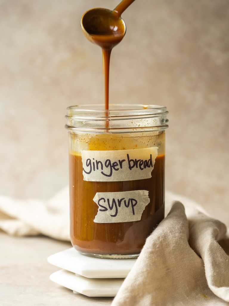Spoonful of gingerbread syrup pouring into a glass jar