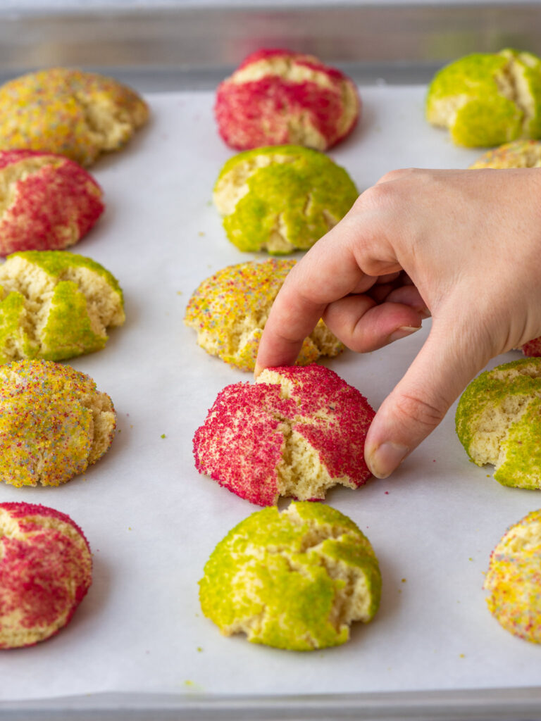 hand grabbing a holiday almond cookie off of  a baking sheet