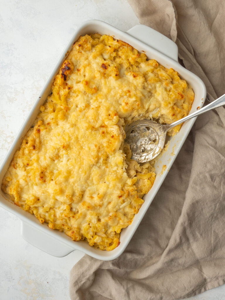 Above view of crab mac and cheese in a serving dish with a serving spoon in it