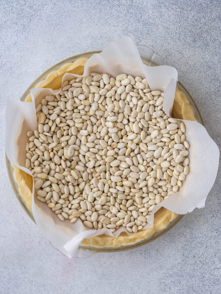 beans on parchment in a pie crust to prebake the crust