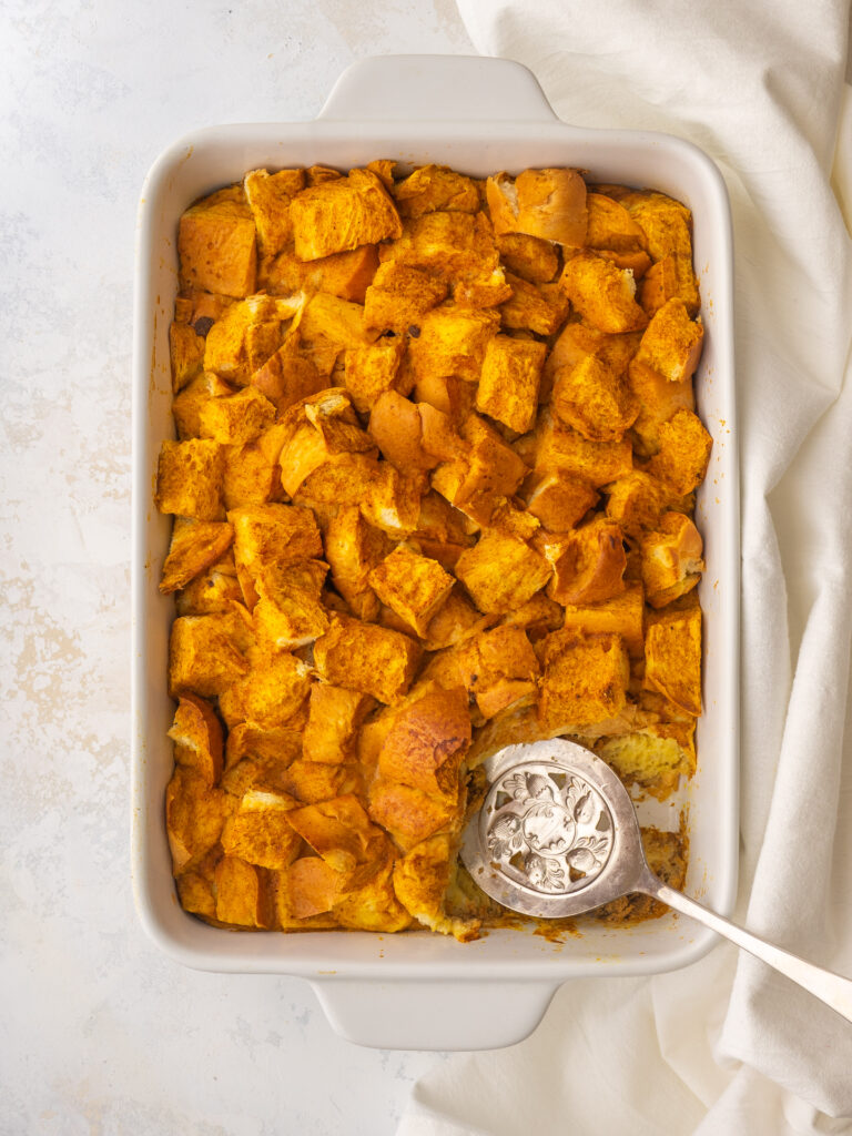 Above view of a challah bread french toast casserole with a serving spoon