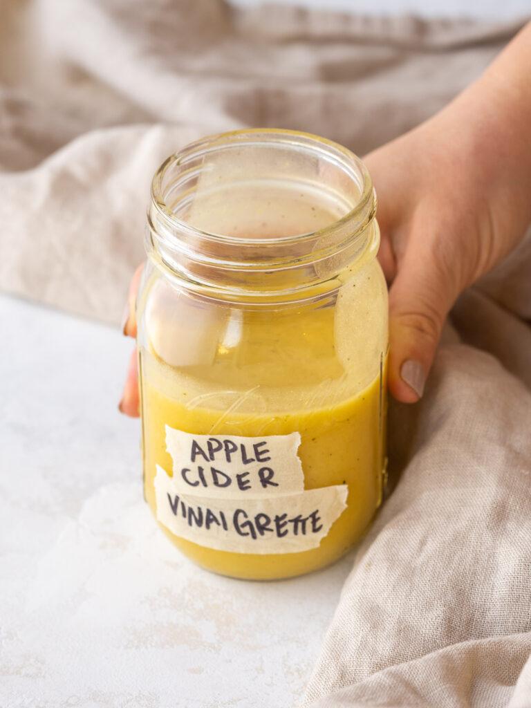 hand grabbing a jar of apple cider vinaigrette