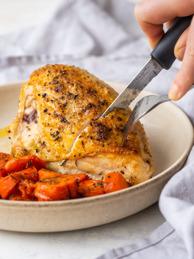 Side view of a knife cutting into a baked chicken breast bone in