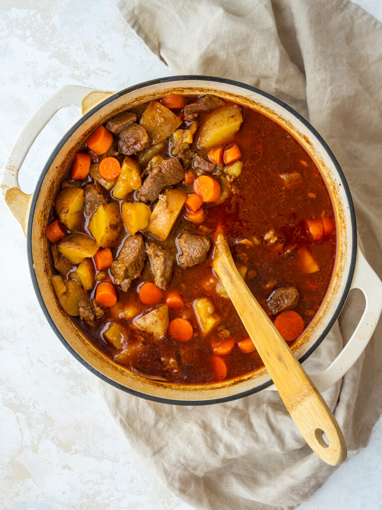 Above view of a pot of Guiness beef stew in a dutch oven with a wooden spoon in it