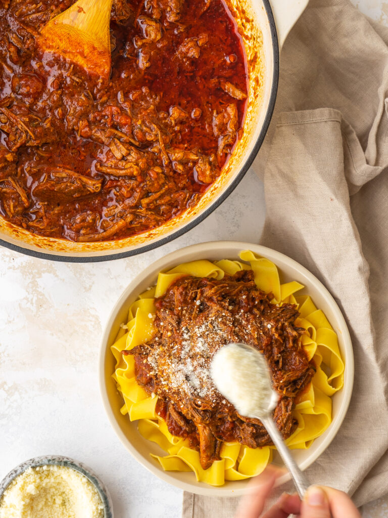 spoon of parmesan cheese shaking over a bowl of pasta sauce made with boneless short ribs