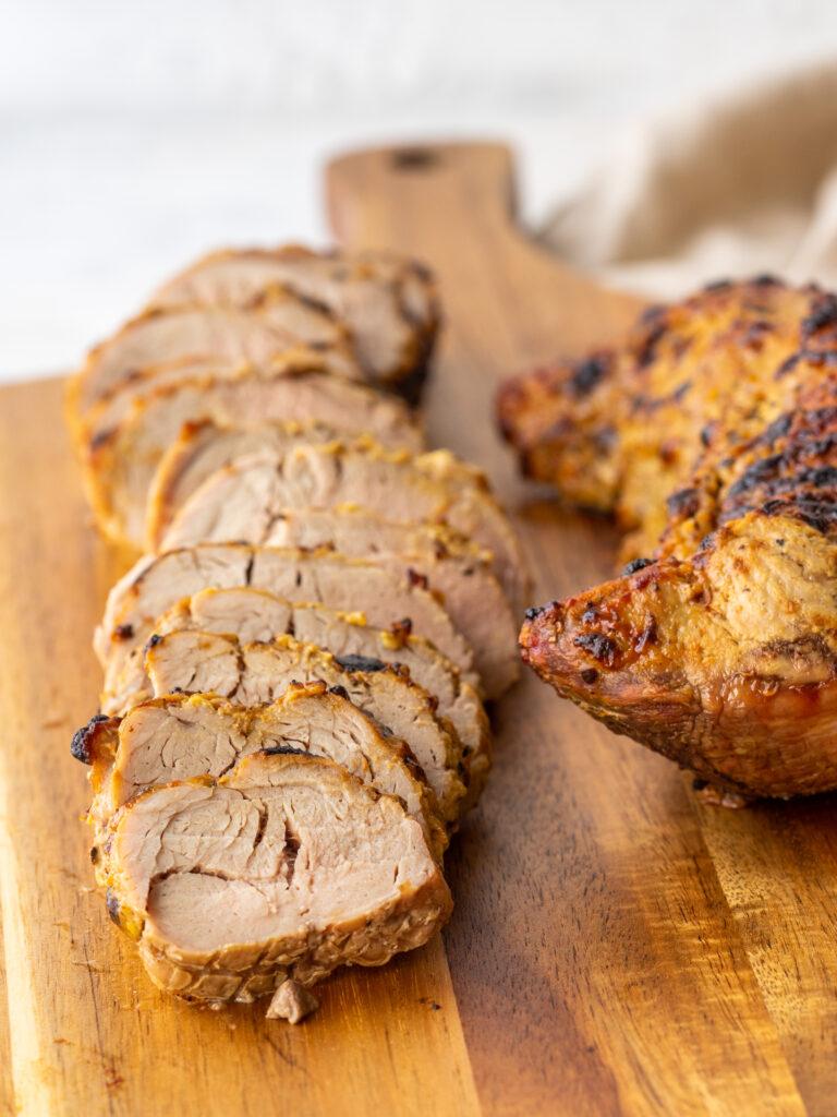 Three quarter view of sliced pork tenderloin in air fryer