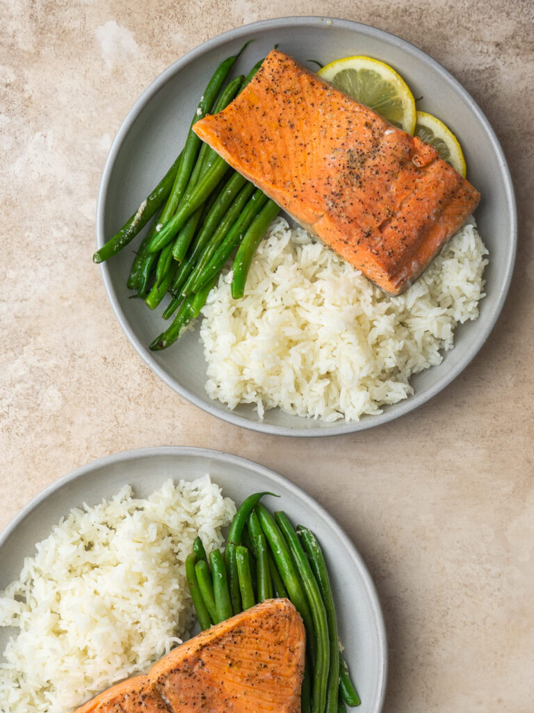 above view of two plates of salmon and rice with green beans and lemon slices
