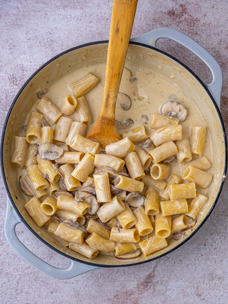 Above view of mushroom alfredo pasta in a pan with a wooden spoon