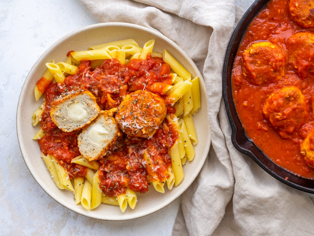 Above view of mozzarella stuffed meatballs on a plate with pasta and marinara sauce