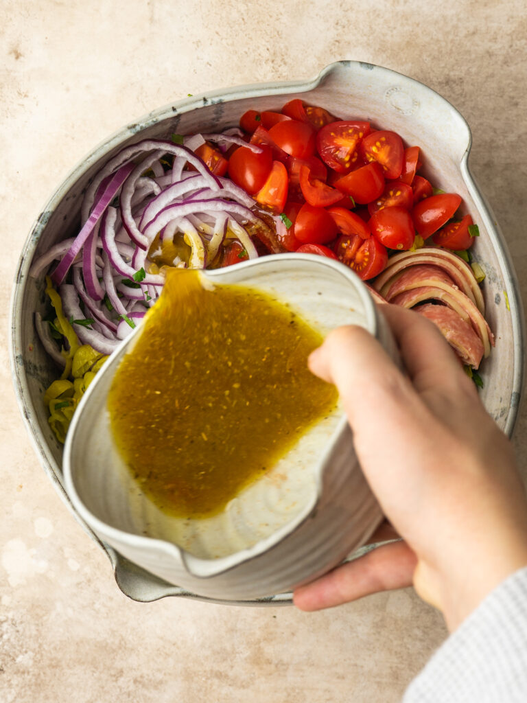 Above view of a homemade Italian salad dressing being poured over an Italian salad