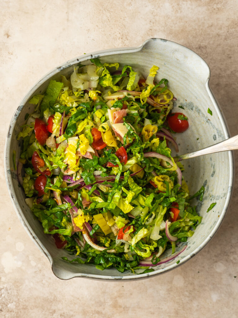 Above view of a tossed Italian Chopped Salad in a mixing bowl