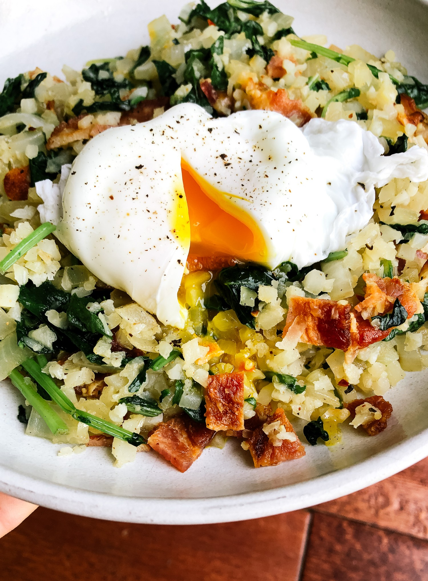 Side view of cauliflower rice stir fry with a poached egg on top