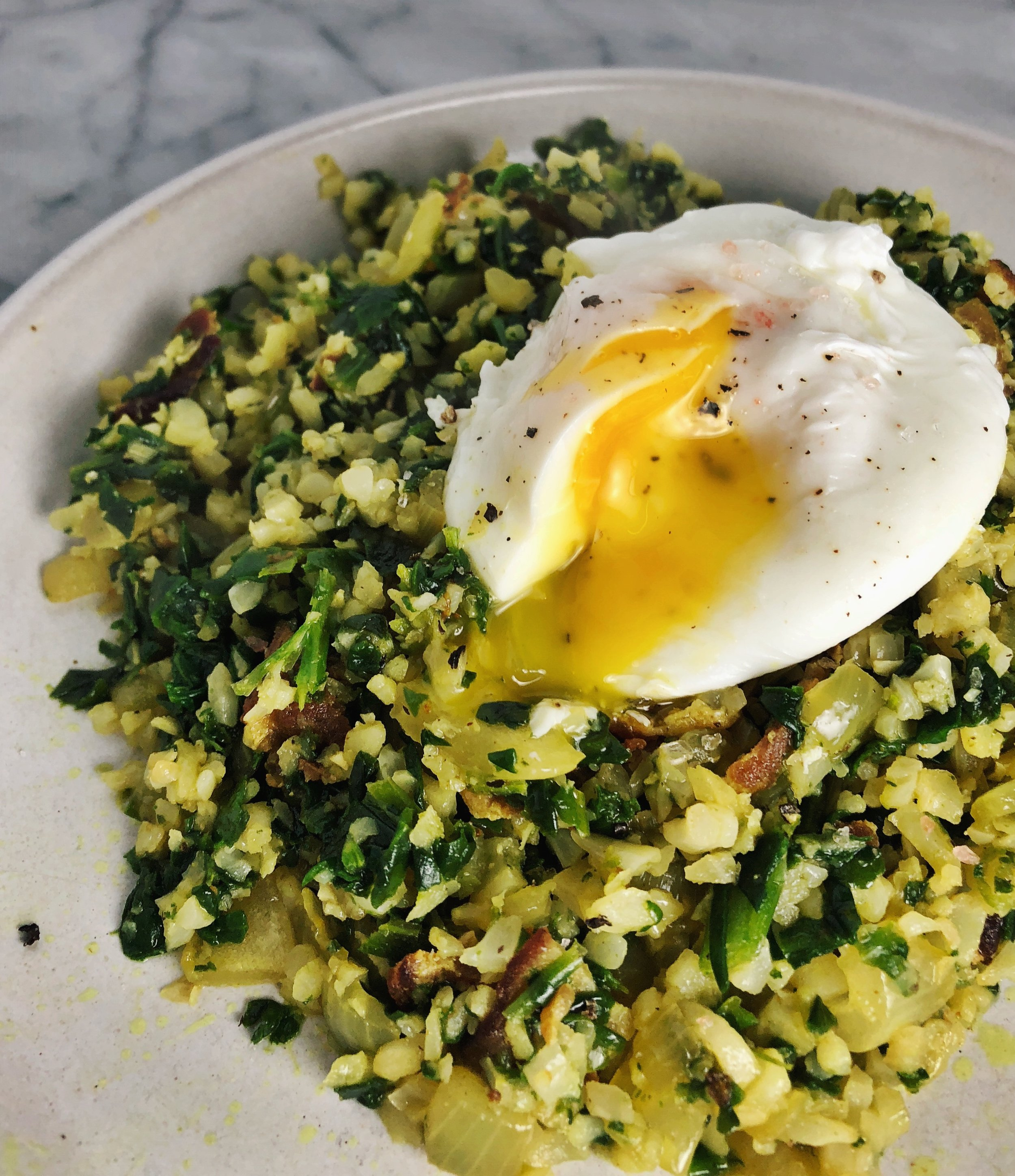 Above view of cauliflower rice stir fry with bacon and a poached egg