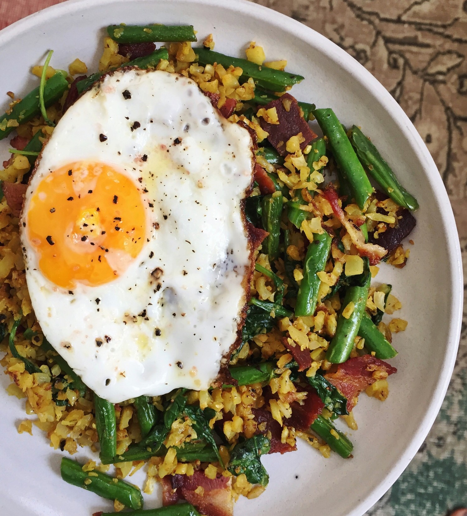 Above view of a cauliflower rice stir fry with bacon and a fried egg