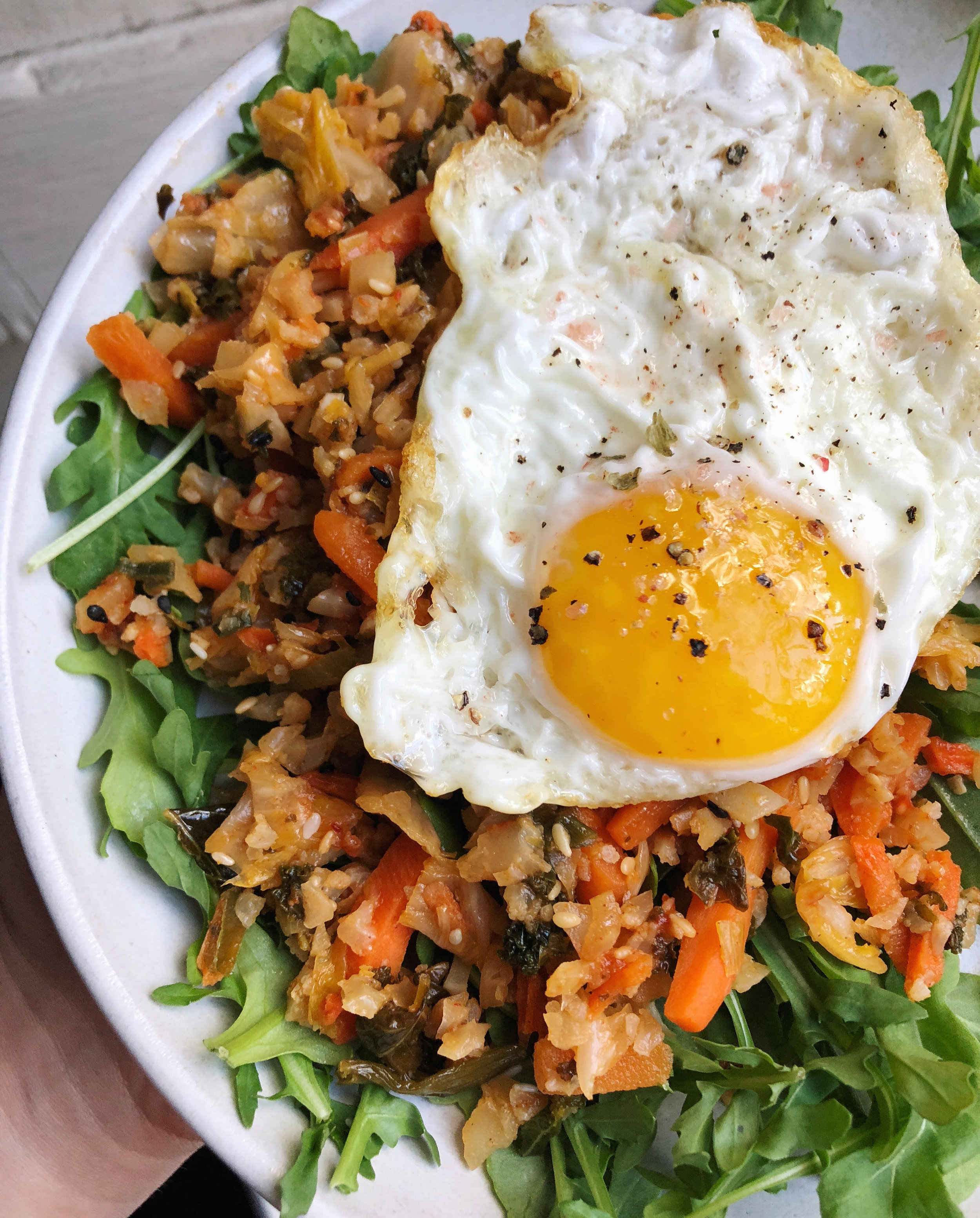 Sunny side up egg on a kimchi and rice stir fry