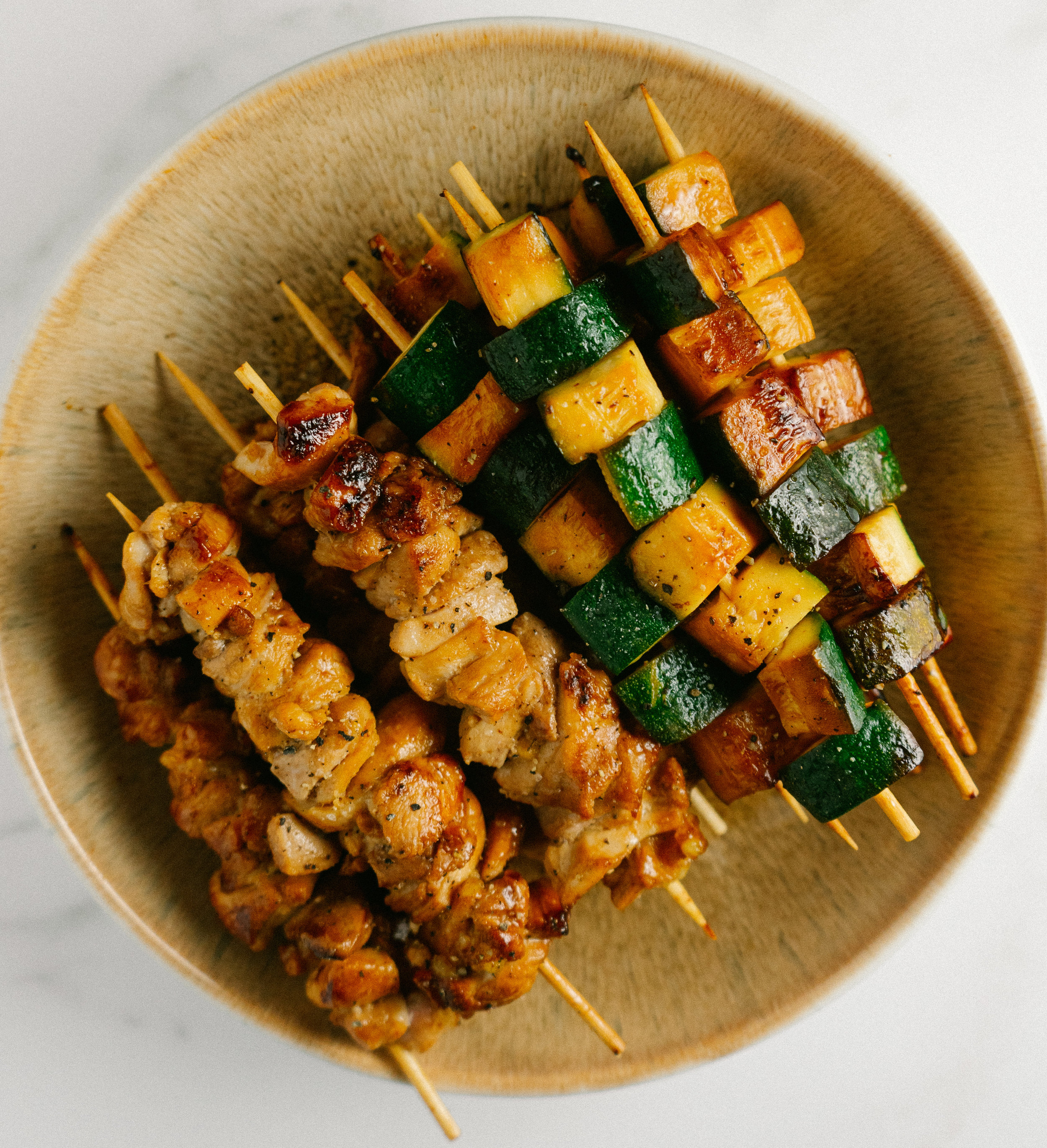 Above view of yakitori chicken and zucchini on a plate