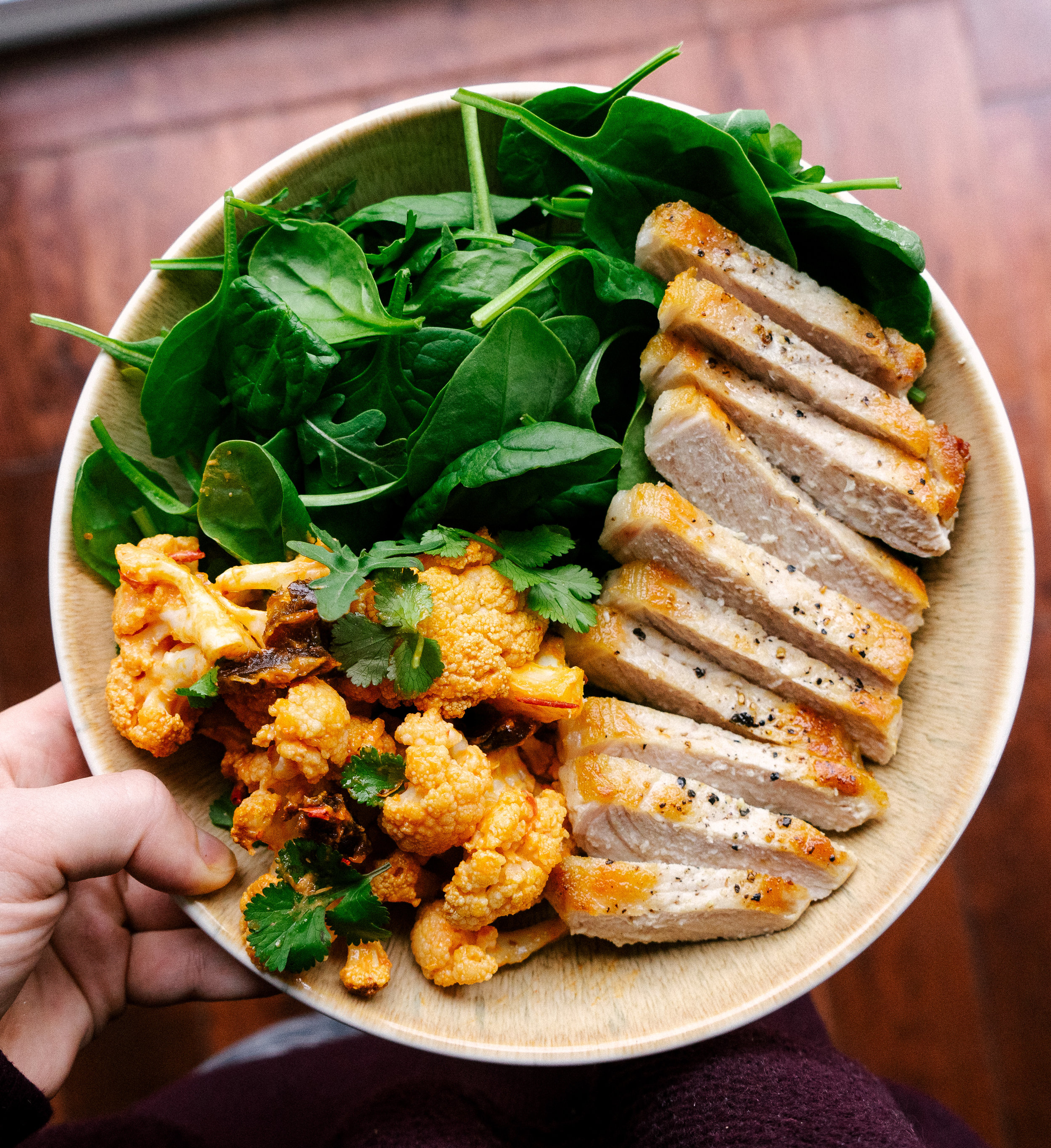 Above view of harisssa roasted cauliflower, seared pork and spinach in a bowl