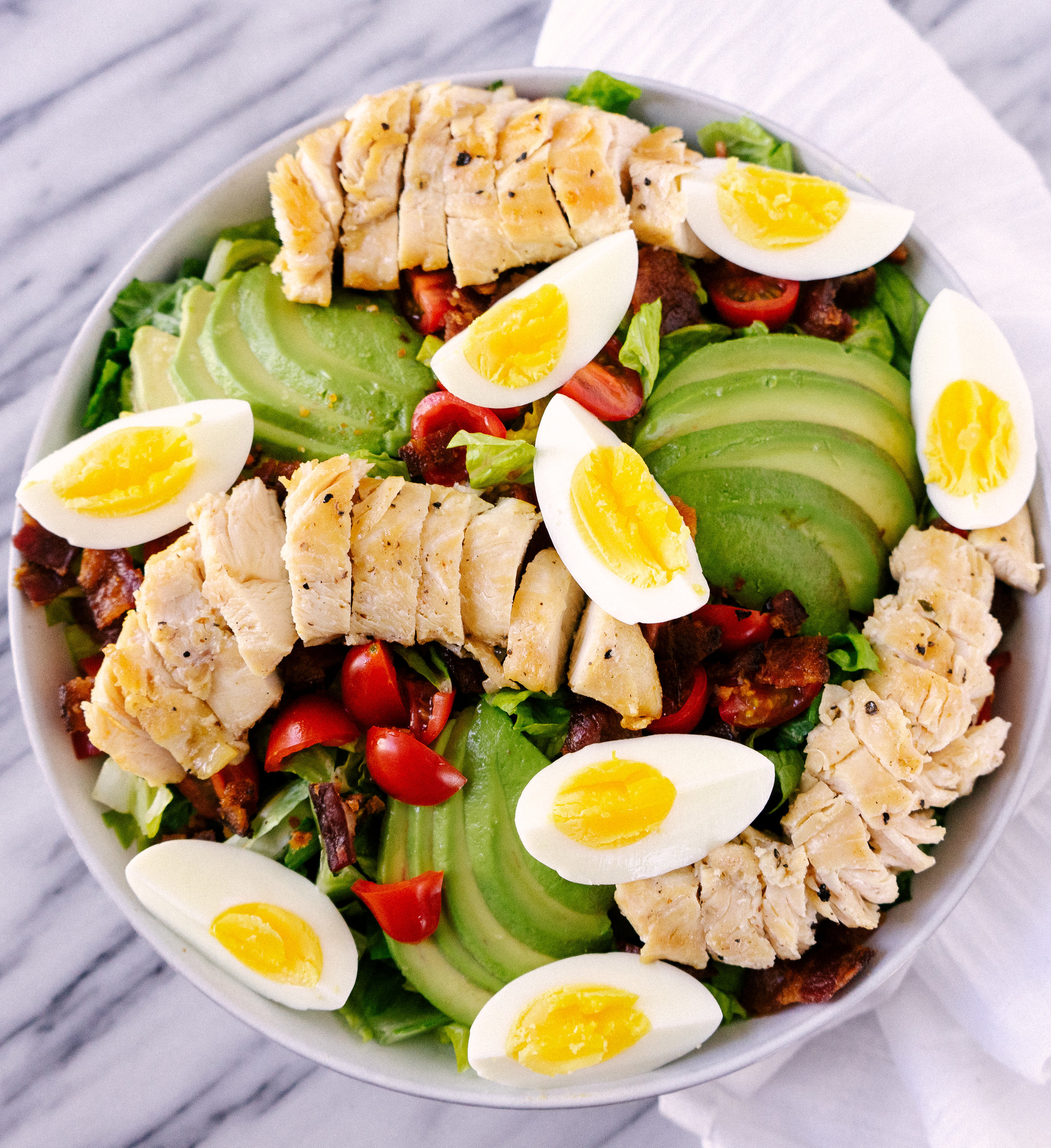 Above view of Whole30 cobb salad with spicy cashew dressing in a serving bowl