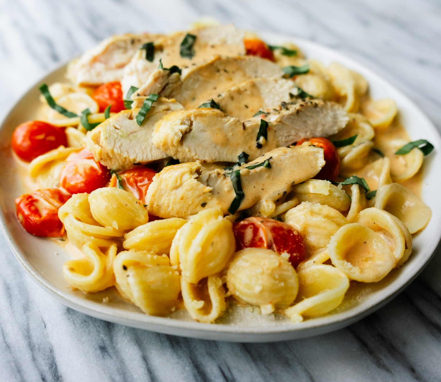 Three quarter view of creamy tomato basil chicken on a plate with pasta