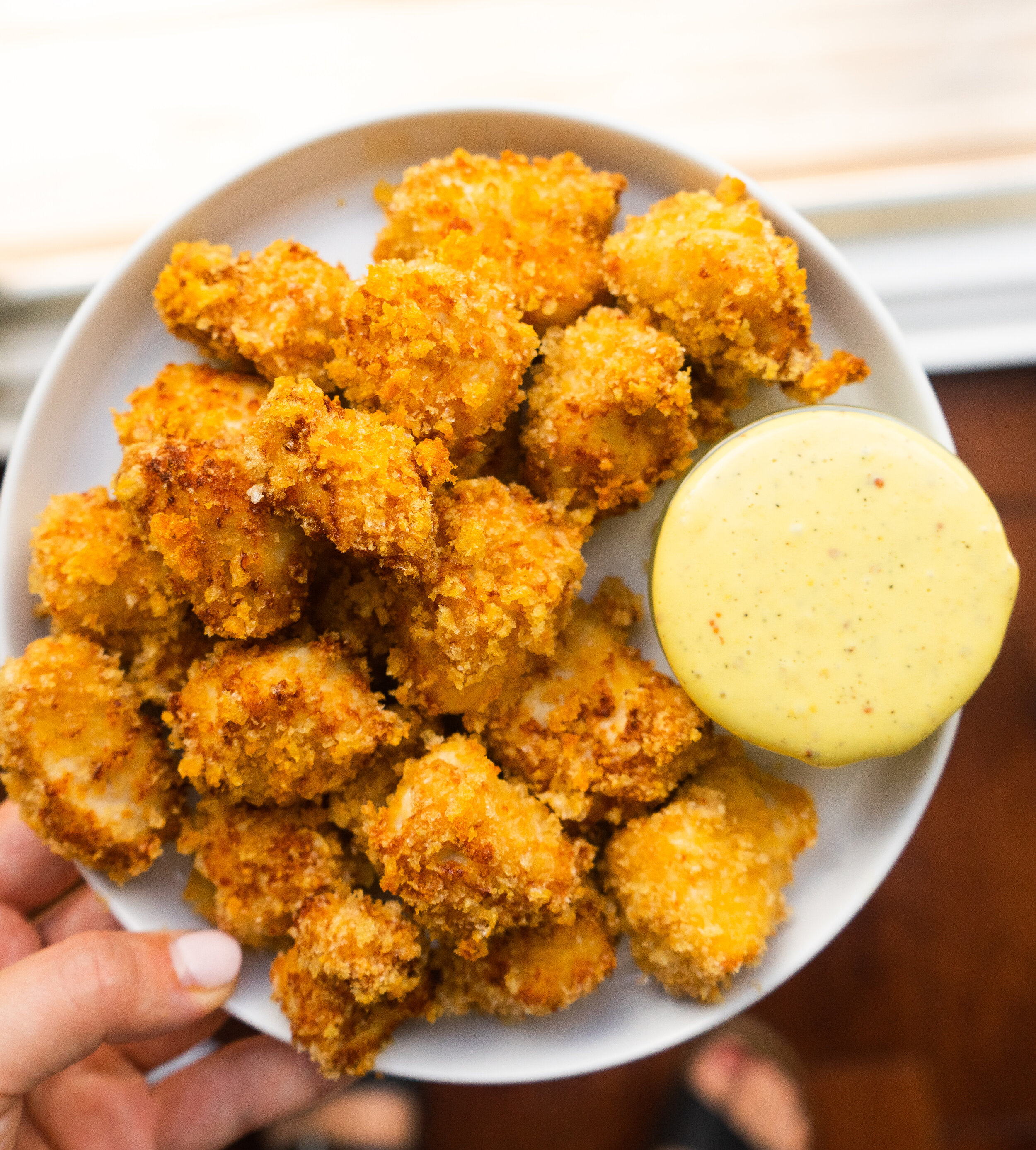Above view of chicken nuggets served with honey mustard on the side
