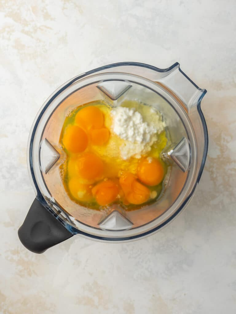 Above view of eggs, cottage cheese and salt in a blender to make egg bite batter