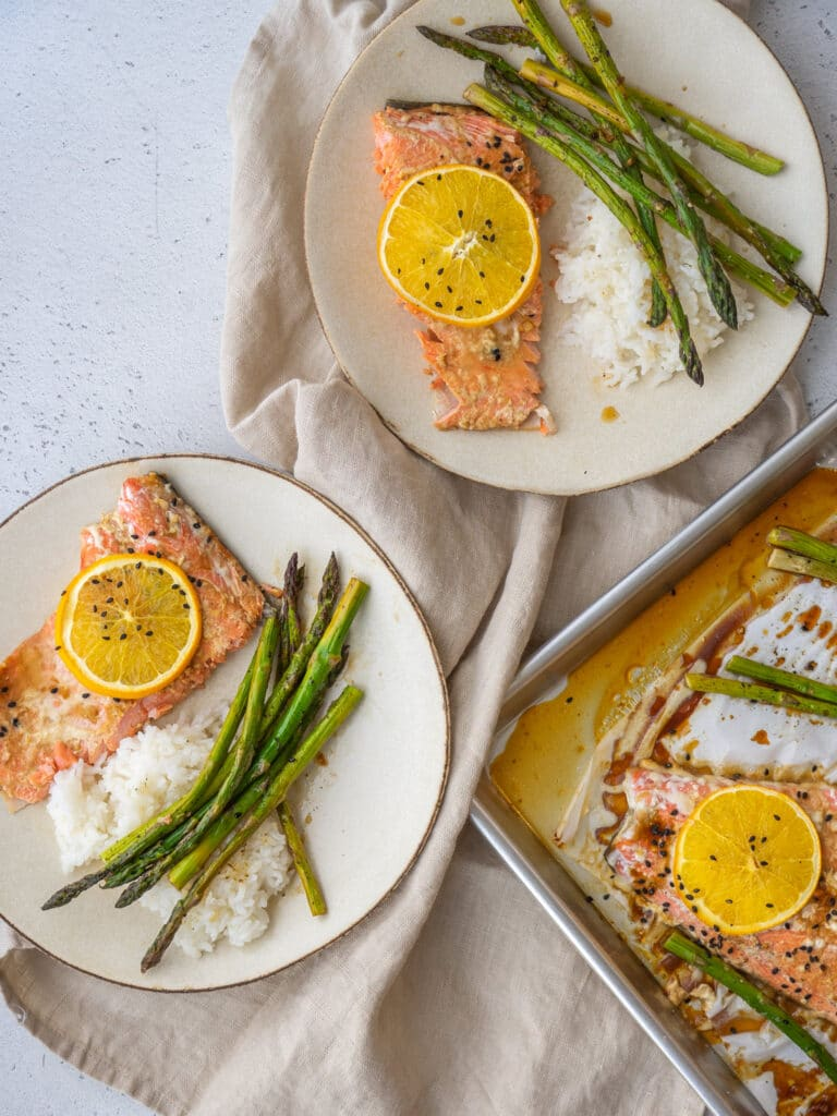 Slices of orange salmon on serving plates with white rice and asparagus
