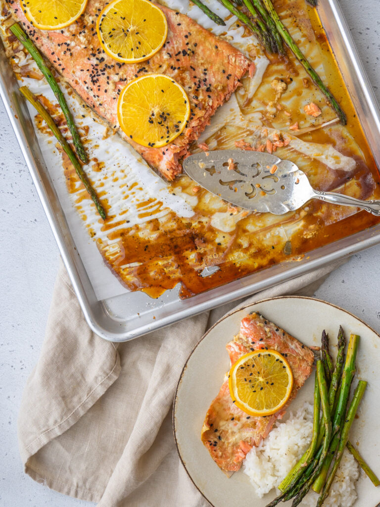 Above view of orange glazed salmon on a baking sheet with a serving utensil