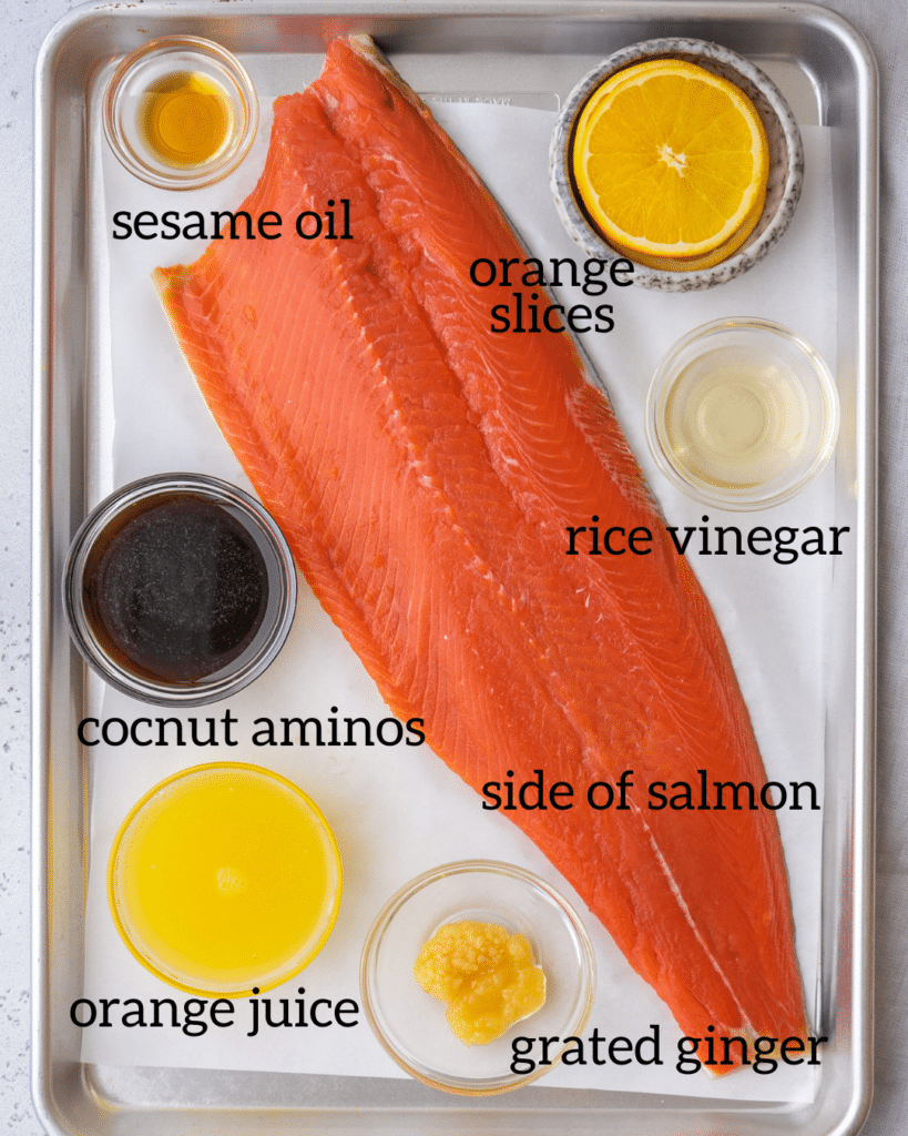 Above view of orange ginger baked salmon ingredients on a baking sheet