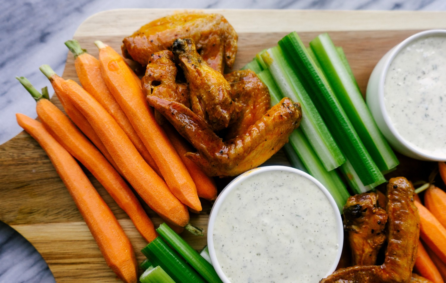 Above view of Whole30 Air Fryer Buffalo wings on a serving platter with ranch dressing, celery and carrots