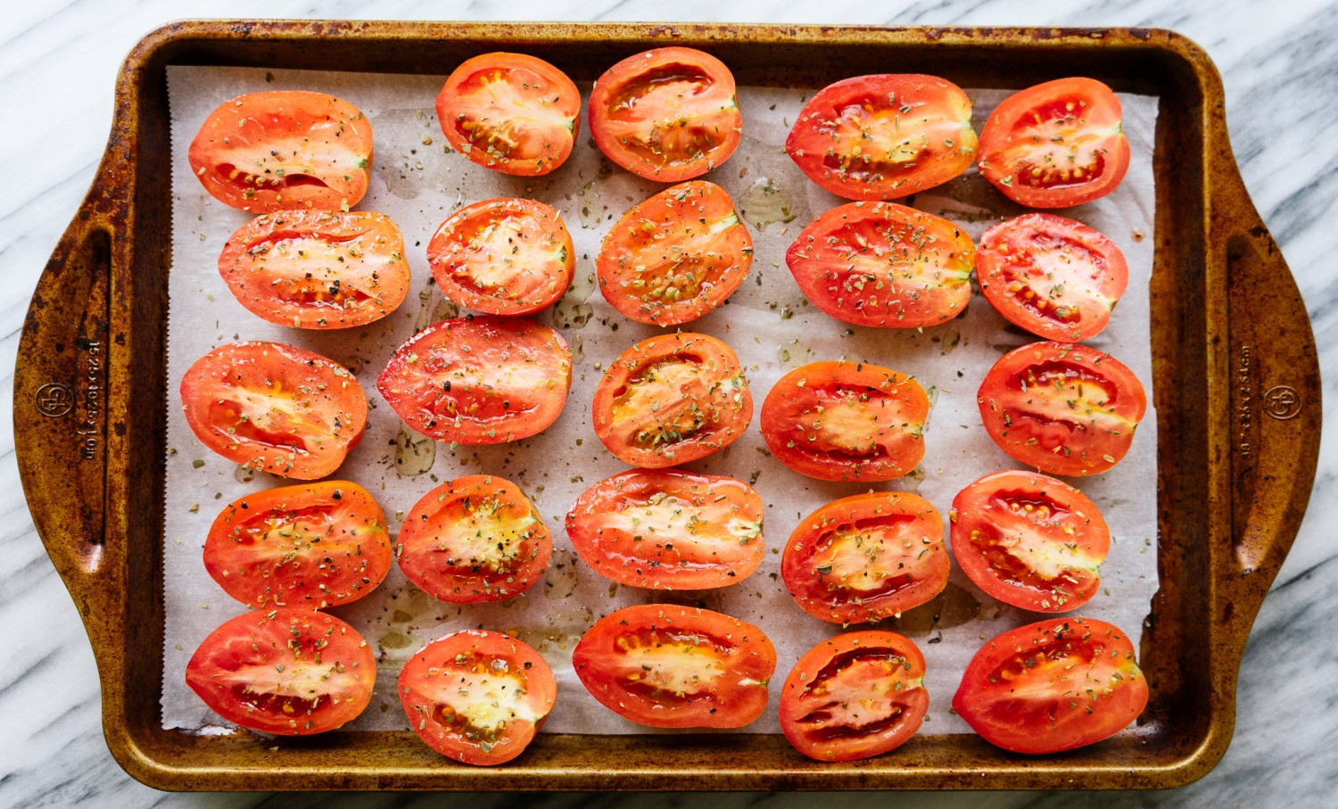 Above view of raw tomato halves on a roasted sheet for a roasted tomato and burrata salad