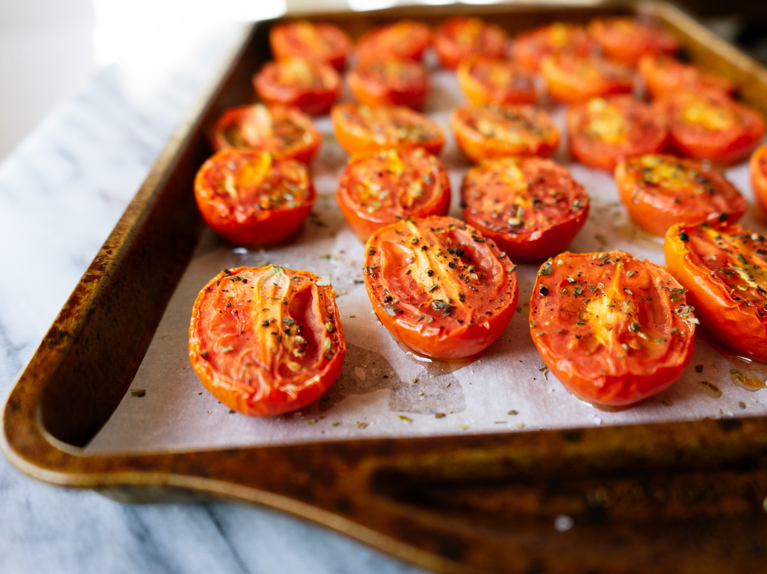 Three quarter view of roasted plum tomatoes on a sheet pan