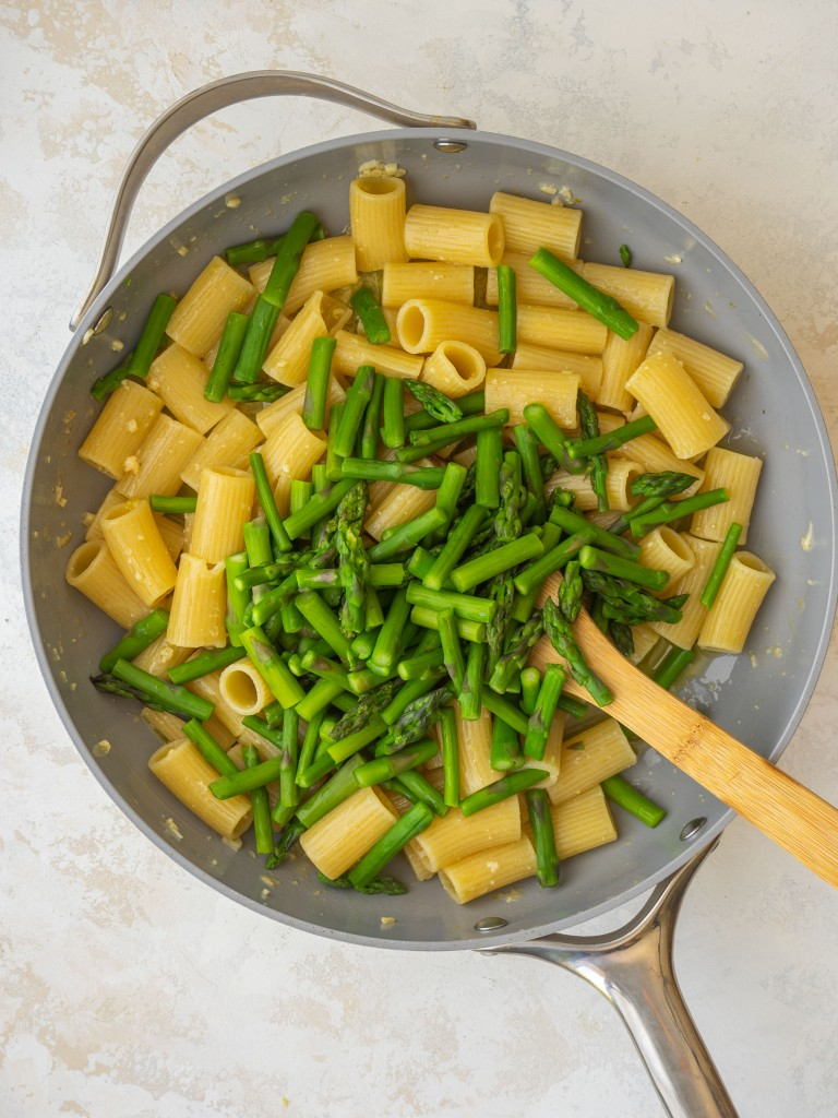 Above view of blanched asparagus in a frying pan with lemon garlic pasta