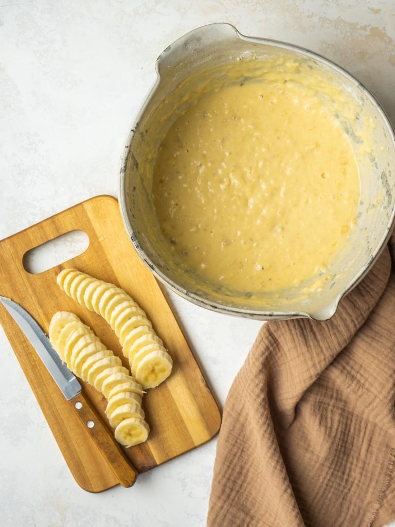 Above view of banana pancake batter in a mixing bowl next to sliced bananas