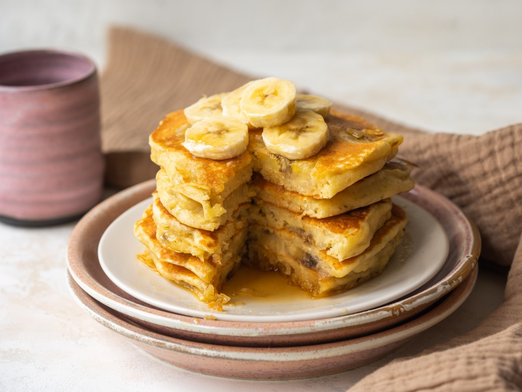 Side view of a stack of fluffy banana pancakes with a slice cut out of them