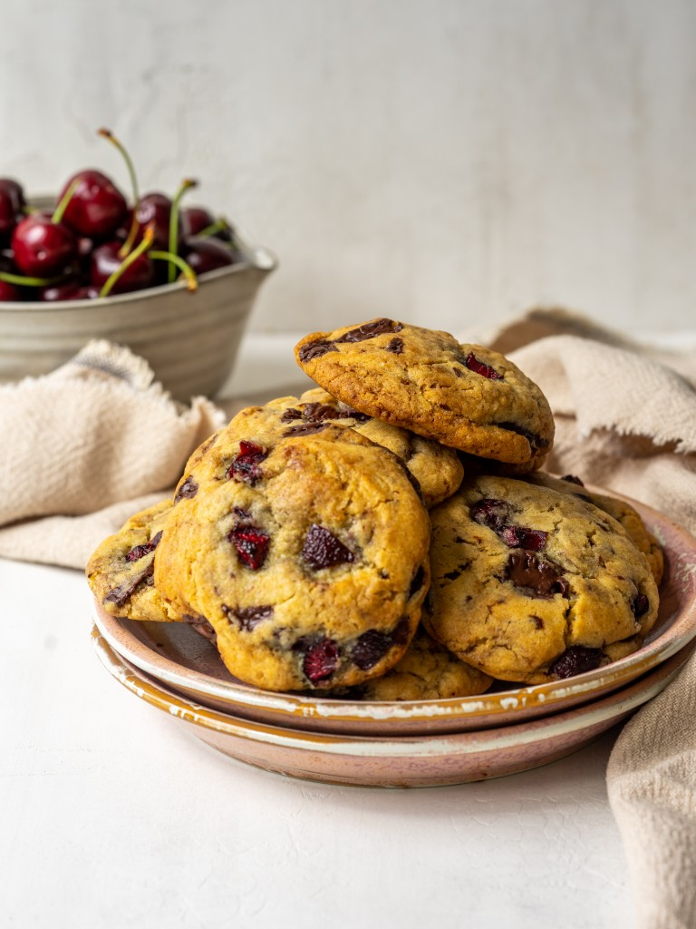 Side view of chocolate cherry cookies on a serving plate with a bowl of fresh cherries in the back