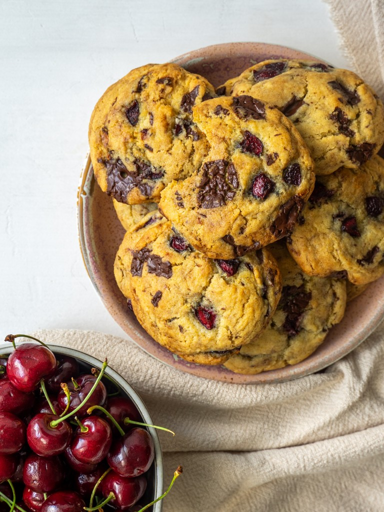 Above view of cherry cookies made with chocolate chunks on a serving plate next to a bowl of fresh cherries
